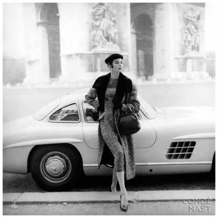 Original caption Model in front of Mercedes, wearing tweed dress, matching coat with fur collar, fur hat, and gloves (all by Patou), holding handbag, with L'Arc de Triomphe in background