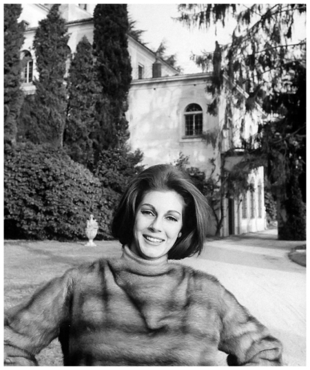 Baroness Fiona Thyssen-Bornemisza, wearing a mink pullover, stands in front of her palace on Lake Lugano in Switzerland, photo by Leonard McCombe, 1963
