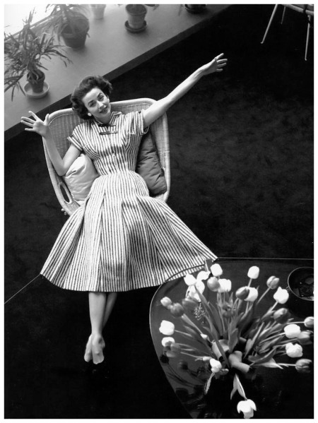 Dorian Leigh in a pleated dress with leather straps by Carven, photo by Georges Dambier, Nouveau Femina, March 1954