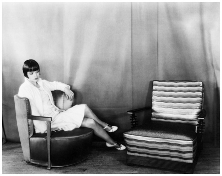 Miss Louise Brooks, movie star, is shown studying the fascinating lines of the modern chair 1928