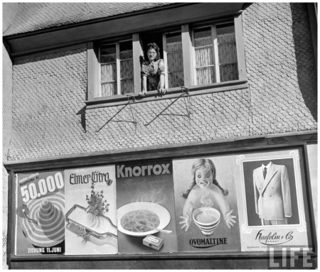 Woman looking out window on Main Street with an advertisment below her Zurich, Switzerland 1948 Yale Joel