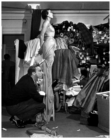 Jacques Fath contemplates the drape of a fabric on a model, photo by Georges Dambier, 1952