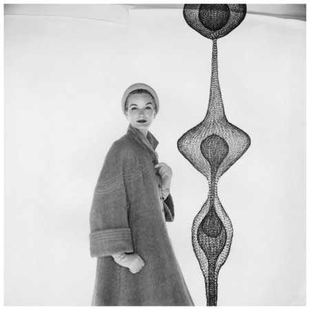 Model, wearing heavy coat with stitched detail at yoke and sleeves, poses beside a wire-mesh sculpture. Circa September 1953 Photo Clifford Coffin