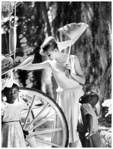 Tania Mallet in creamy-beige dress with sleeveless fringed bodice and double pleated skirt by Susan Small, photo by Vernier in Nassau, Vogue UK, January 1961