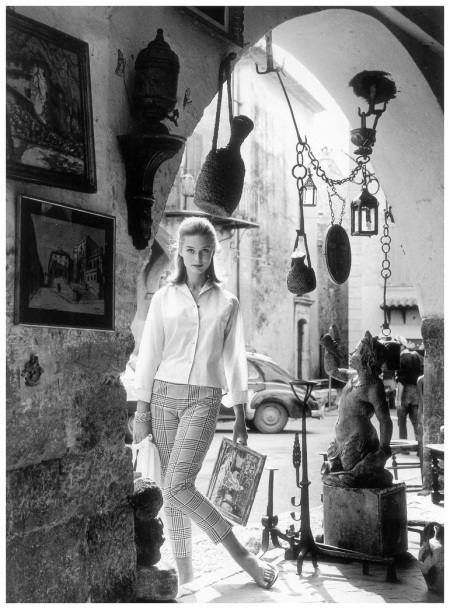 Tania Mallet in Prince of Wales checked cotton trousers by Slimma and pale blue cotton batiste by London Pride, photo by Vernier in Biot, in the south of France, Vogue, July 1960