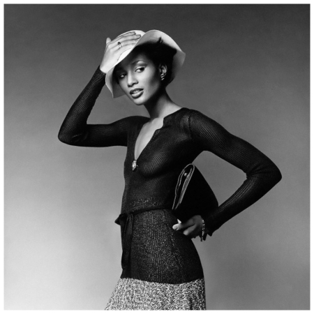 1974 NYC, USA Model Beverly Johnson wearing a sheer ribbed pullover with low neck and sashed waist by Ross-Zeldin, a tweed knit flared skirt by Scott Barrie, and holding a flat envelope bag by I. Miller - Image by Francesco Scavullo