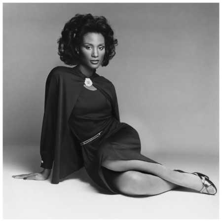 Beverly Johnson wearing a dark matte slip dress with thin rhinestone belt and buttonless cardigan by Adele Simpson, latched at the collar with a Van Cleef & Arpels diamond pin. Circa February 1974 Francesco Scavullo
