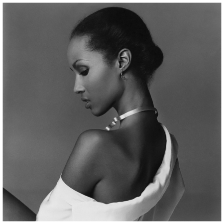 Iman wearing an off-the shoulder white blouse and gold band necklace; her hair is pulled back Francesco Scavullo