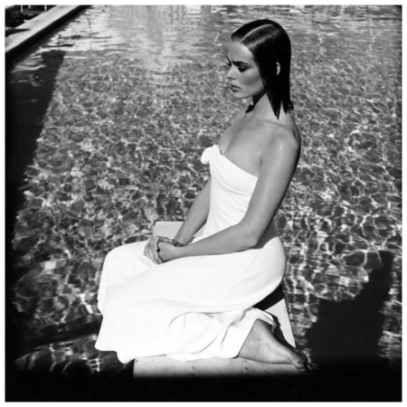 Margaux Hemingway sitting on the diving board at the Beverly Hills Hotel pool, wearing a strapless white terry beach dress by Carol Horn for Bendel's Studio 1975 Francesco Scavullo Beverly Hills Ca