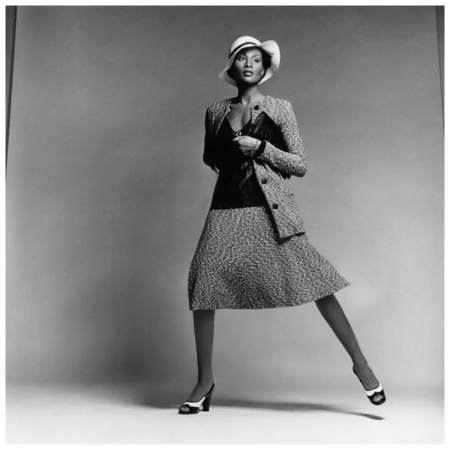 Model Beverly Johnson wearing a tweed sweater suit with long button-front cardigan, matching flared skirt and sheer ribbed pullover by Scott Barrie, with a hat by Don Marshall and envelope bag by I. Miller. Circa February 1974 Francesco Scavullo