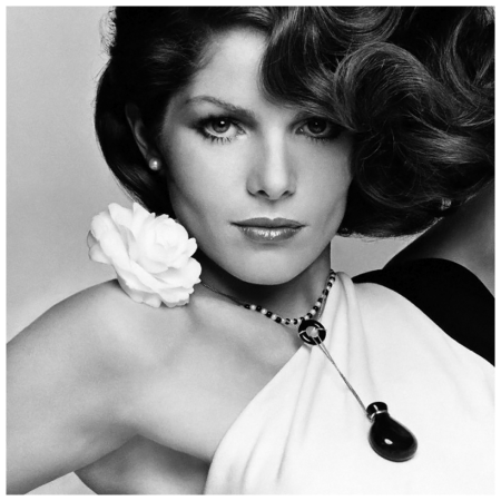 Model Lois Chiles, wearing a black and white rayon crepe one-shouldered dress by Halston with a fresh camellia flower on the shoulder and a onyx and pearl necklace with bottle pendant by Elsa Peretti 1974 Francesco Scavullo