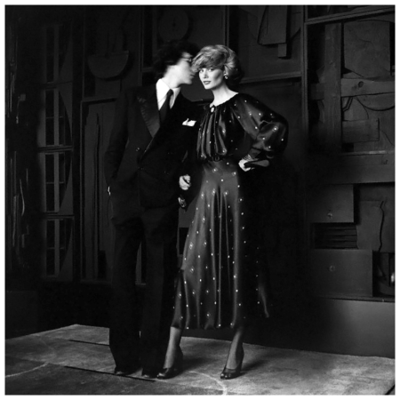Model, standing with a man before a Louise Nevelson sculpture, and wearing an ankle-length, black silk satin print dress with bloused bodice by John Anthony 1974 Francesco Scavullo