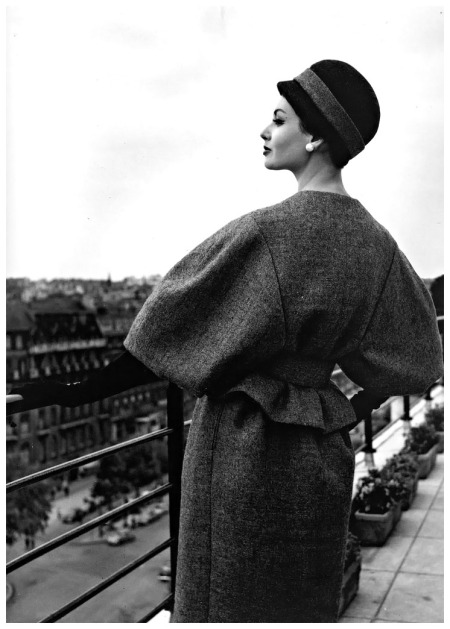 Katherine Pastrie in grey flannel suit with the jacket's belted waist accentuating the full sleeves, cloche in black felt with grey flannel band, Crahay for Nina Ricci, 1959, photo by Willy Maywald, Paris