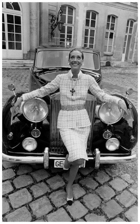 Marisa Berenson, leaning on grill of a Rolls Royce, wearing a Chanel skirt suit, with crucifix medallion on chain, and belt Photo Arnaud de Rosnay 1969