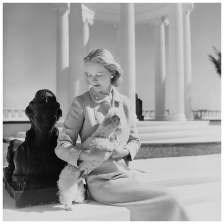 Mrs. Winston Guest wearing Mainbocher suit at the Villa Artemis, the house of her mother-in-law, Mrs. Frederick Guest. She holds a small pet dog and sits beside a sphinx. Photo Cecil Beaton March 1951