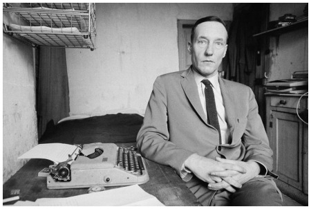 American writer William Burroughs works on his novel The Soft Machine in his room in Paris, 1960