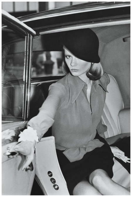 Kourken Pakchanian Manhattan, New York City,1973 Model wearing a chiffon blouse tied at the waist and dark, worsted skirt by John Anthony, with a dark felt hat pulled over one eye by Don Anderson, emerging from a Rolls Royce