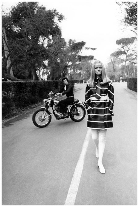P Man on Ducati350motorbike on the Fontana dei Cavalli Marini, at the Villa Borghese, wearing black shirt and trousers, with snakeskin belt and Carlo Palazzi scarf, and Veruschka wearing black and white striped cire raincoat by Fabiani 1969 Franco Rub