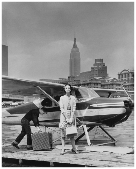 P Photo John Rawlings Mrs. Amory Carhart Jr. wearing a Fair Isle print linen dress as an unidentified man unloads her Louis Vuitton suitcases 1954