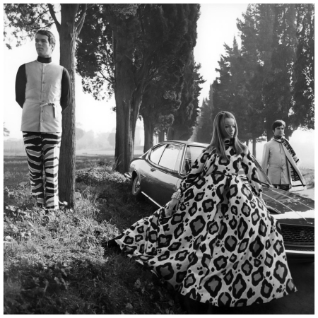 P ,Veruschka wearing large leopard print pajama gown, standing next to a Fiat Dino, with Max Brunell, left, and Carlo Ortiz, right, Franco Rubartelli 1969 Condé Nast Archive