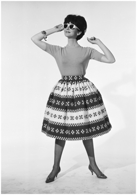 A sixties fashion model wearing a calf-length patterned skirt, broadly designed and flaring out from the hips, March 1961