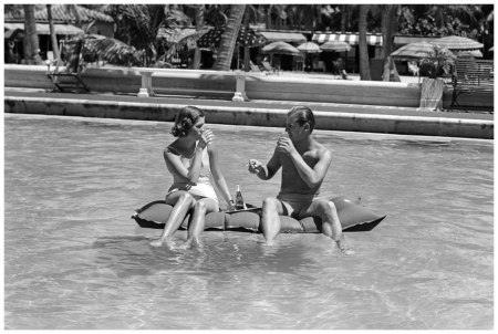 Couple Sitting On A Float In A Swimming Pool Wearing Bathing Suits Holding Drinks In their Hands Smiling Spectator Serving Tray Sparkle. (Photo by H. Armstrong Roberts:Retrofile:Getty Images) 1940's