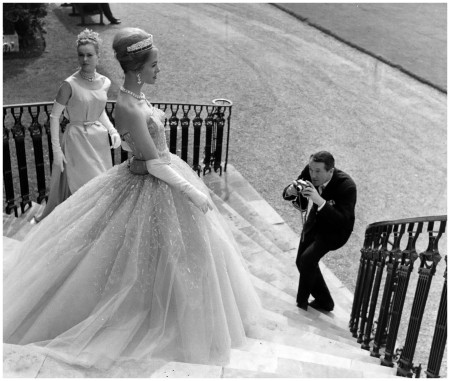 English couturier and dressmaker to the Queen, Hardy Amies,photographs two of his models, wearing his creations - March 1960