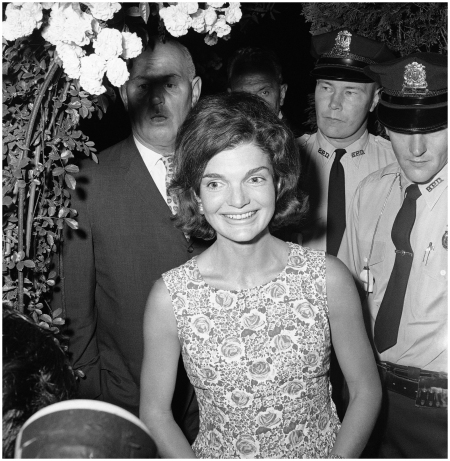 Jackie Kennedy, 1960-Mrs. John F. Kennedy smiles talking to newsmen wearing a floral print shift dress