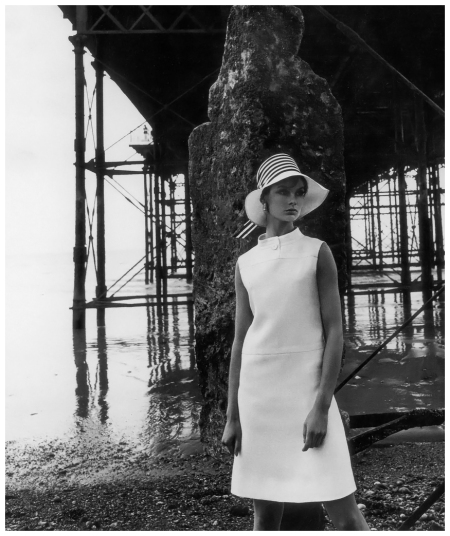 Jean Shrimpton in simple white linen dress by Susan Small, hat by Simone Mirman, photo by Vernier under the Brighton Pier, Vogue UK, July 1966