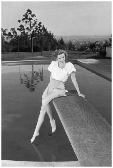 Portrait of Judy Garland dressed in a short skirt and blouse, seated on the diving board of an outdoor swimming pool. She is stretching her leg to touch the surface of the water nd Corbis