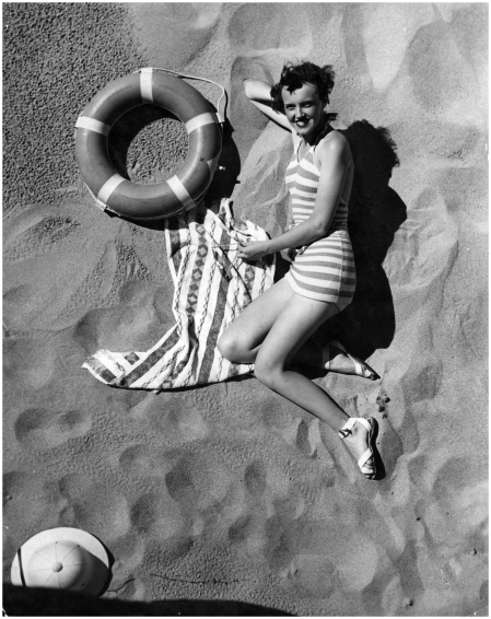 A surf girl relaxes on Palm Beach, Australia, beside a life-ring, 1935
