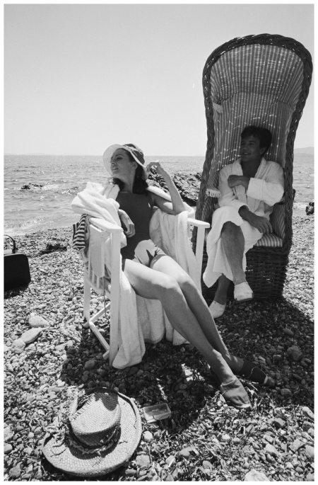 Actors Albert Finney and Audrey Hepburn relaxing on the beach during filming for Stanley Donen's 1967 Two For The Road