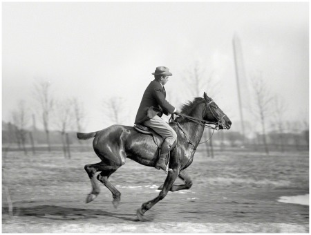 Washington, D.C., 1914. %22Wrisley Brown, attorney, riding.%22 You'll note the Washington Monument showing a decided tilt to the left, although the reason is more optical than political. Harris & Ewing glass negative.
