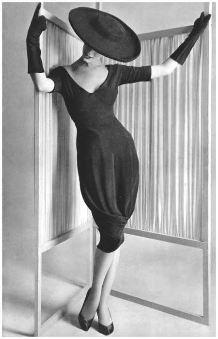 All the interest lies in the barrel skirt with the drape caught at the bottom, of black crêpe, worn by Simone, designed by Grès, photo by Philippe Pottier, 1958