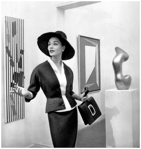 Model in elegant blue wool suit that buttons to an attached white bib by Manguin, hat by Claude St. Cyr, handbag by Le Marchand, photo by Pottier at Galerie Denise René, 1957
