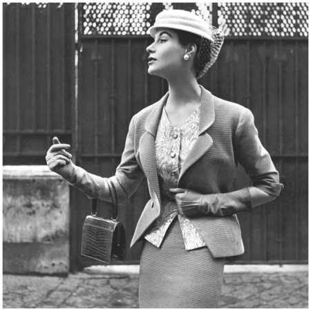 Myrtle Crawford in beige Ottoman suit with fitted jacket indented to v, worn over print cashmere top and narrow skirt by Manguin, hat by Paulette, croc bag by Morabito, photo by Pottier, 1953