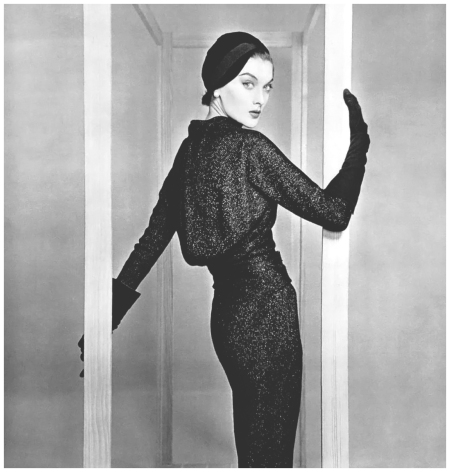 Rose Marie in woven black metal jersey dress, the blouson top is draped at the waist, narrow sleeves and pencil skirt accentuates the sinous line, by Jacques Fath, photo by Pottier, 1954