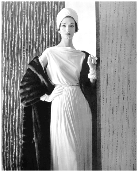 Simone d'Aillencourt in supple, softly draped and pleated crêpe dress by Pierre Balmain, worn with mink coat, photo by Pottier, 1957