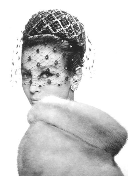 Sophy Derly in small toque with silver and black mesh on black velvet by Paulette, earrings by Francis Winter, fur by Chombert, photo by Pottier, 1961