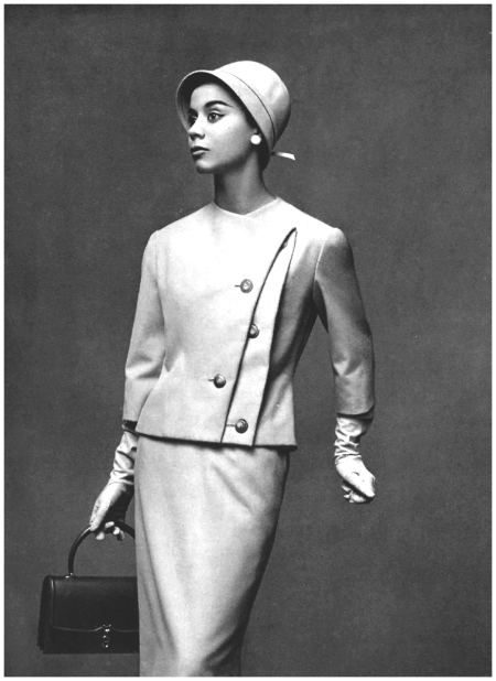 Model in light gray wool suit, interesting jacket has double buttoned edge, slightly oblique, by Jean Dessès, purse by Hermès, photo by Georges Saad, 1957