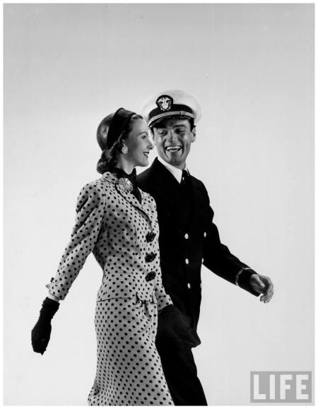 Model wearing polka dotted suit & straw cloche hat walking w. model dressed in uniform of US Navy officer Photo Gjon Mili 1943 NYC