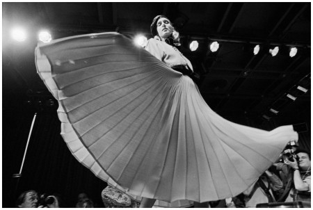 A model fans a Nina Ricci pleated skirt on the runway, 1986. Photograph by Abbas:Magnum