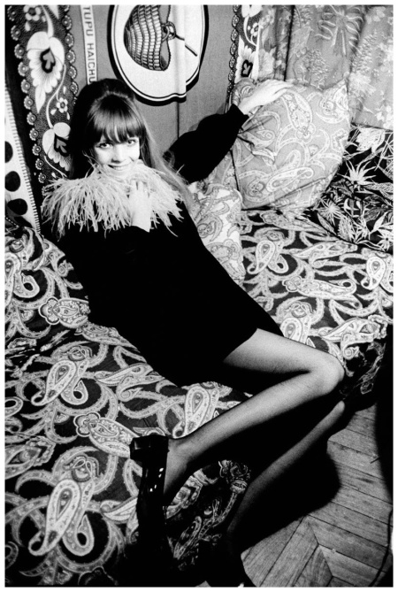 Penelope Tree reclining on a paisley-covered couch, wearing black velvet minidress with ostrich fringe Baron Arnaud De Rosnay 1967