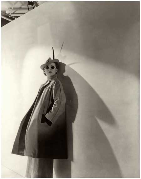 A model wears round sunglasses, Model wearing a wool polo coat and mustard felt hat, both by Molyneux 1936 Photo Cwecil Beaton