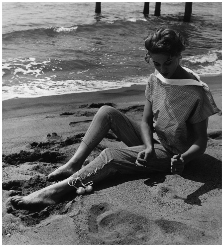 A woman sitting on the beach wearing blouse and trousers by Fabiani. Italy, August 1952 (Photo by Mondadori Portfolio via Getty Images)