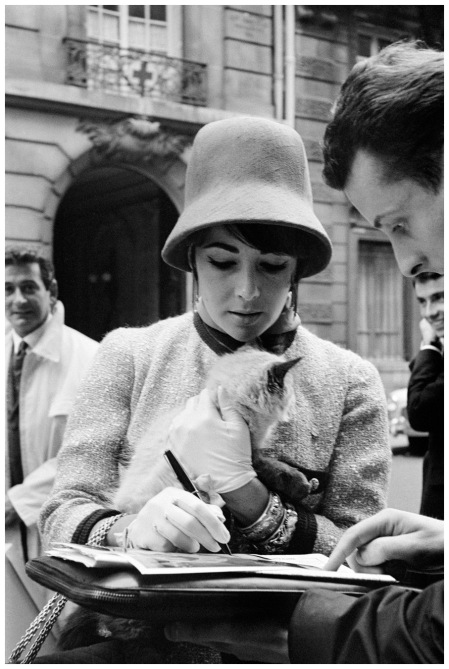 Elizabeth Taylor While returning to Paris from a trip to Russia in 1961, Taylor proved herself capable of simultaneously signing an autograph and stroking the nape of a mysterious cat Henri Bureau:Corbis