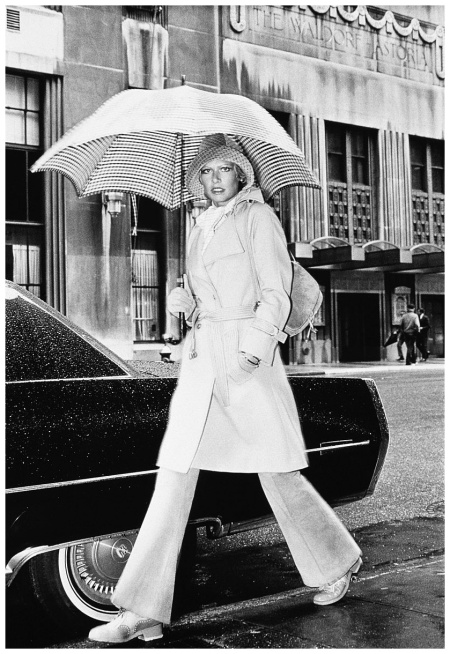 Model, walking with an umbrella by Givenchy, wearing a wool gabardine trenchcoat by Christian Aujard over shirt by Ralph Lauren and pants by Leslie Fulop, Adolfo hat and Walter Katten bag, gloves by Bonnie Cashin Photo Kourken Pakchanian