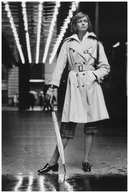 Model wearing a Weatherbee poplin trenchcoat over rolled-up plaid pants and checked socks, holding umbrella NYC 1973 Condé Nast Archive Photo Kourken Pakchanian