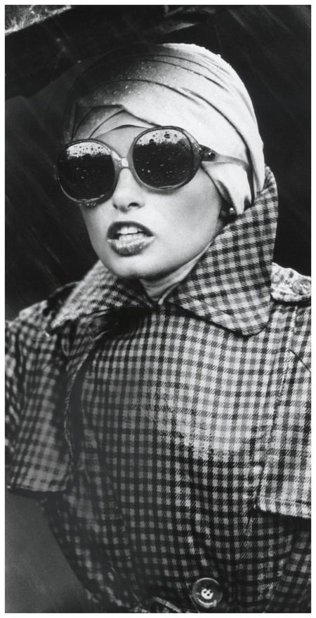 Model wearing tattersall trenchcoat by Tom Fallon, with large sunglasses and chambray turban by Don Anderson for Scheer Bros 1972 Photo Kourken Pakchanian