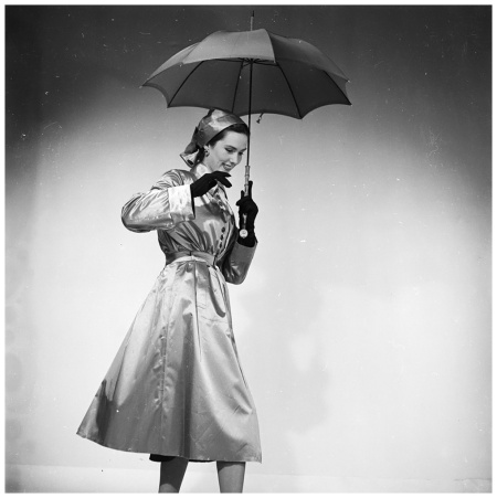 Rain Ensemble A belted raincoat buttoned to the waist, worn with a turban style hat in the same material. (Photo Chaloner Woods:Getty Images) 1953